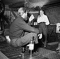 Man en vrouw, wijn drinkend en sigaretten rokend aan boord van het schip Siegfri, Bestanddeelnr 252-9413.jpg