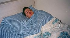 Man sleeping striped-sheets.JPG