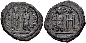 Theodosius (son of Maurice) - Copper follis from the Cherson mint, showing Maurice, the empress Constantina, and Theodosius holding a staff surmounted with the Chi-Rho.