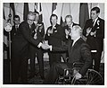 Mayor John F. Collins shakes hands with an unidentified man (12773929355).jpg