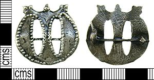 Pilgrim badge - A medieval cast lead alloy monogram of Maria pilgrim badge. The badge is in the shape of a Lombardic 'm' with crown above. The crown is formed of three projections; the two outer projections are trefoil and the central is a single collared knop. The outline of the 'm' has a beaded border and in the gaps between the columns of the 'm' the casting seam can be seen. The reverse of the badge is plain; the catchplate has survived intact but only the stump of the pin remains