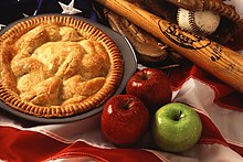 An apple pie, apples, a baseball bat, a baseball and a baseball glove on top of an American flag