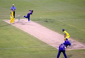 A bowler in a blue uniform bowls a white cricket ball to a batsman dressed in a yellow uniform and dark-blue helmet.  An umpire in a light blue shirt and cream, wide-rimmed hat watches, along with another batsman, at the other end of the pitch.  A wicketkeeper is kneeling close behind the batsman receiving the ball, and a slip fielder is standing behind and to his left, with his hands on his knees.