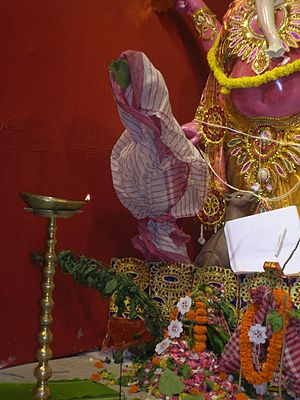 Consorts of Ganesha - Kola Bou (Banana wife) dressed in a white-red sari placed near the Ganesha image in a Durga Puja
