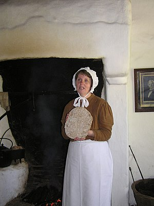 Oatcake - An oat cake being displayed by an employee of the Ulster American Folk Park, near Omagh, in County Tyrone, Northern Ireland, in a demonstration of their preparation