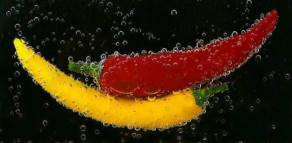 Red and yellow bell peppers in water