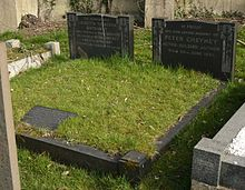 Two polished, black granite headstones surrounded by other gravestones