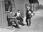 Pilots of No. 19 Squadron relax between sorties outside their crew room at Manor Farm, Fowlmere, near Duxford, September 1940. Left to right- Pilot Officer W Cunningham, Sub-Lieutenant A G Blake of the Fleet Air Arm and CH1459.jpg
