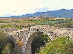 Photographie d'un ancien pont à arches avec un paysage agricole et champêtre ainsi que des collines en arrière-plan.