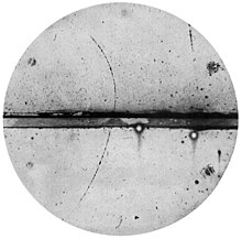 track of subatomic particle moving upward through cloud chamber and bending left (an electron would have turned right)