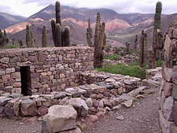 small stone structure, with cacti and mountains in the background