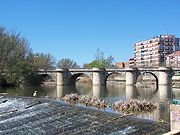 Photo depicts a stone bridge with five arches crossing a river.