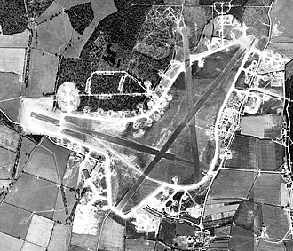 RAF Grafton Underwood - Aerial photograph of Grafton Underwood airfield. The bomb dump is to the north of the perimeter track on the west side of the airfield. 22 April 1944.  Note the large number of 384th Bomb Group B-17s on hardstands.