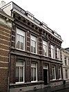 Herenhuis met in de gevel overvloedige toepassing van hardsteen voor waterlijsten, versiering boven de vensters en middenfronton in de verdieping