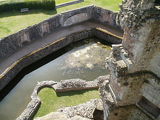 Raglan Castle - The view from the top of the Great Tower, showing the thick walls, the remains of the apron wall and a turret, the moat, the moat walk and a space for a classical statue