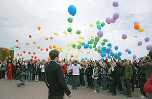 Large group of people releasing multicolored balloons