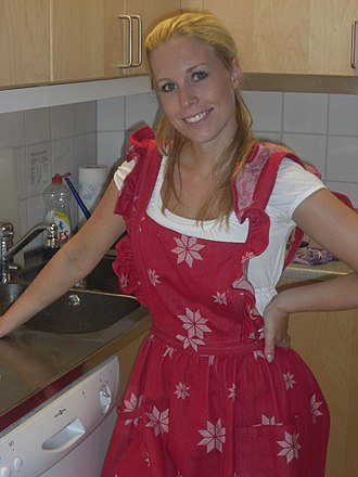 Apron - Woman wearing an apron next to a stove in a kitchen
