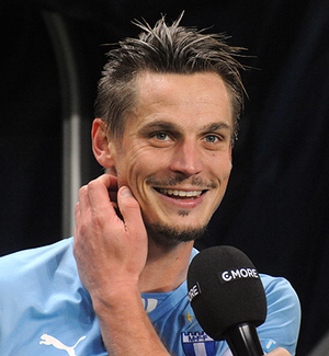 A zoomed in photograph of a man with sprawling hair and stubble, dressed in a sky blue football shirt. He is smiling brightly and itching his right cheek. He is in the process of being interviewed by a man outside the frame who is extending a black microphone.