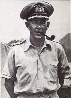 Outdoor half-length portrait of man in light-coloured military uniform with peaked cap, smoking a pipe