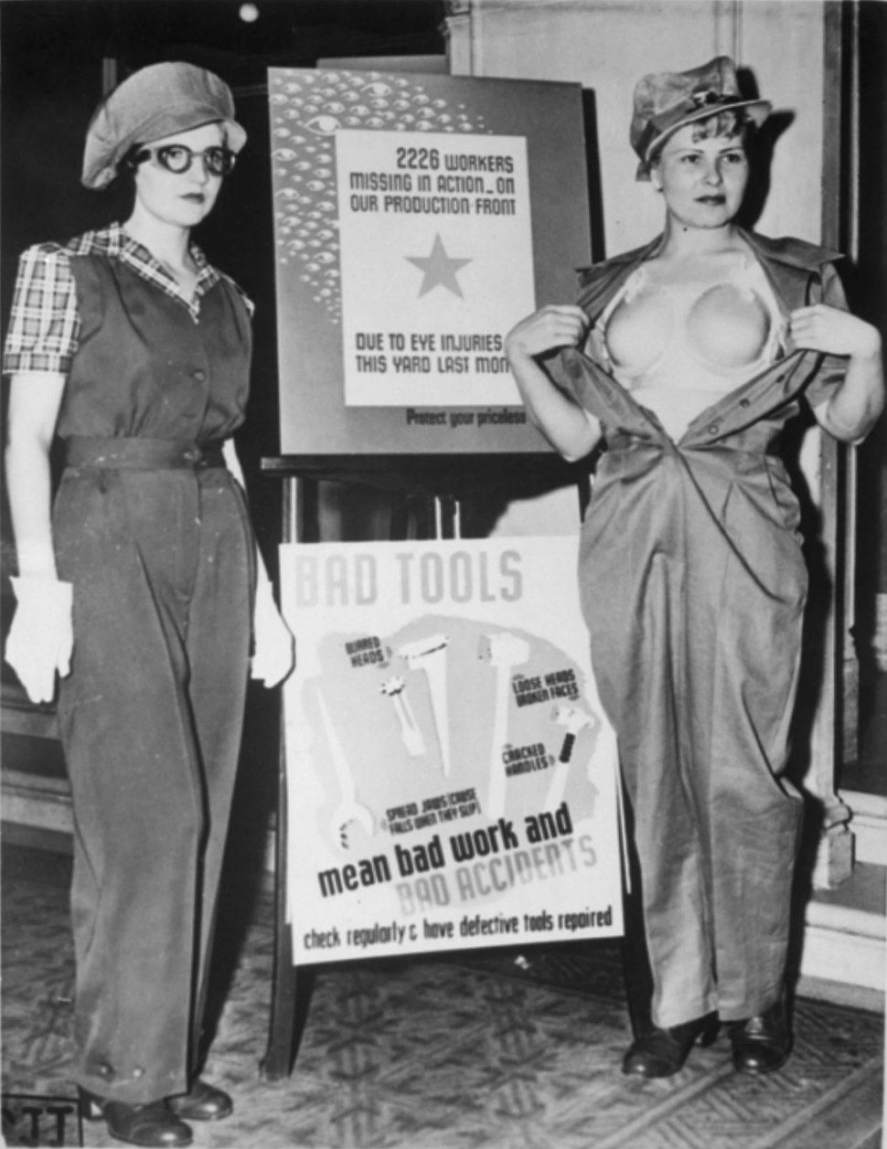 """Safety garb for women workers. The uniform at the left, complete with the plastic """"bra"""" on the right, will prevent... - NARA - 522882"""