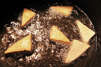Shallow frying - Triangular slices of tofu being shallow-fried in rice bran oil