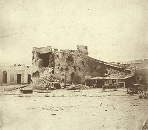 Photograph of a large, ruined masonry tower within a fortress that is pockmarked with large shell holes and two artillery caissons sitting in the foreground