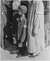 Six-year-old war orphan with Buchenwald badge on his sleeve waits for his name to be called at roll call at... - NARA - 531302.tif