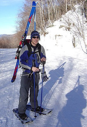 A snowshoer packing downhill skis Snowshoer packing skis.jpg