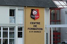 Photographie du logo du Stade rennais et de l'inscription « Centre de formation E.T.P. Odorico ».