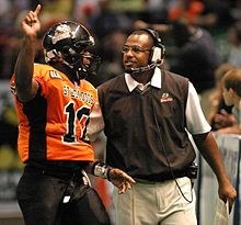 An American football player in an orange jersey and black helmet speaks with a coach in a black sweater.