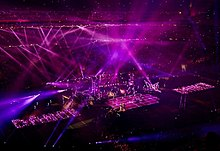 A faraway image of a stage with purple lights flashing from all around on it.