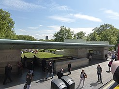Entrance and shelter on Piccadilly, a green copper roof spans between two stone structures with a view of a park between