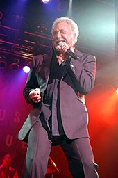 A grey-haired bearded man wearing a grey suit, singing into a microphone
