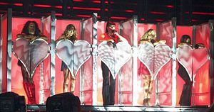 Too Much (Spice Girls song) - The group performing the song behind neon pink-colored, heart-shaped doors in Las Vegas.