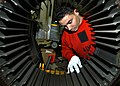 US Navy 030930-N-7090S-001 Aviation Ordnanceman 2nd Class Elijah L. Rhodes from Baltimore, Md. cleans the inside drum palette of a M-61 20 MM.jpg