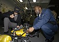 US Navy 050207-N-6214F-001 Damage Controlman 2nd Class Devon Williams, right, and a Board of Inspection and Survey (INSURV) inspector checks a Self Contained Breathing Apparatus (SCBA) aboard the amphibious assault ship USS Iwo.jpg
