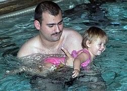 Un homme moustachu dans une piscine tenant dans ses bras une enfant en maillot rose