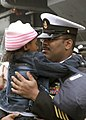 US Navy 071127-N-0483B-006 Chief Aviation Electronics Technician (SW-AW) Gerald William holds his daughter during a homecoming ceremony for the aircraft carrier USS Kitty Hawk (CV 63), shortly after the ship arrived at Commande.jpg