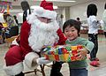 US Navy 091220-N-XXXXX-001 Petty Officer 1st. Class James Durrance acts as Santa during a visit to distribute toys to children of the Misono Orphanage.jpg