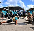 US Navy 100514-N-8433N-226 oatswain's Mate 3rd Class Cote Laflamme encourages a Southern High School student attempting to do 50 push-ups while wearing a 23-pound flak vest.jpg