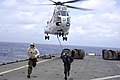 US Navy 101021-N-8335D-371 Service members run for safety after hooking a pole pendant to an SA-330j Puma helicopter during a vertical replenishmen.jpg