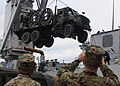 US Navy 111118-N-WJ771-256 Marines assigned to Combat Logistics Regiment 3 watch as a medium tactical vehicle replacement is loaded into the well d.jpg
