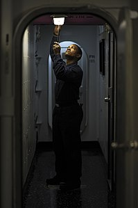 US Navy 120130-N-XE109-018 A Sailor performs maintenance on a light fixture.jpg