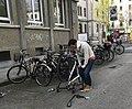 Une personne regonflant un pneu de son vélo à Genève.JPG