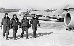 Vietnam People's Air Force - Pilots walk past MiG-17s on the flight line