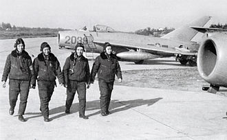 Vietnam People's Air Force - Pilots walk past MiG-17s on the flight line