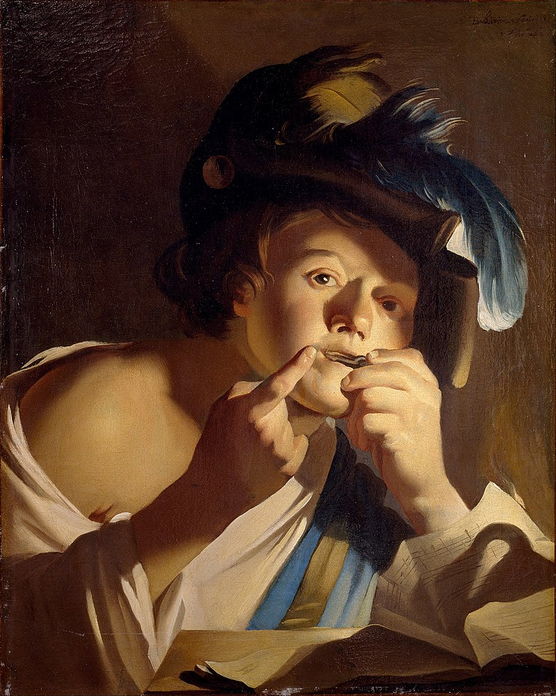 Boy plucking a Jew's harp with his fingers