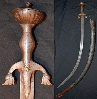 Pulwar - Afghan pulwar, 19th century mounts, earlier (17th to 18th century) deeply curved 82 cm blade of damascus watered steel, inlaid on one side with maker's mark and Islamic inscription, other gold inlays throughout the blade, large iron hilt with characteristic down turned quillions and brass rivet caps, inside measurement 104 cm, leather over wood scabbard with iron chape.