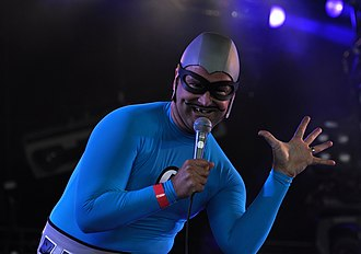 "The Aquabats - As part of the band's superhero image, each member of The Aquabats adopted a stage name and backstory. Christian Jacobs' alter ego is ""The MC Bat Commander"", whose trademark look includes a drawn-on mustache and blacked-out tooth."