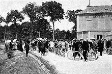 Photographie en noir et blanc montrant un attroupement sur une route devant une auberge.